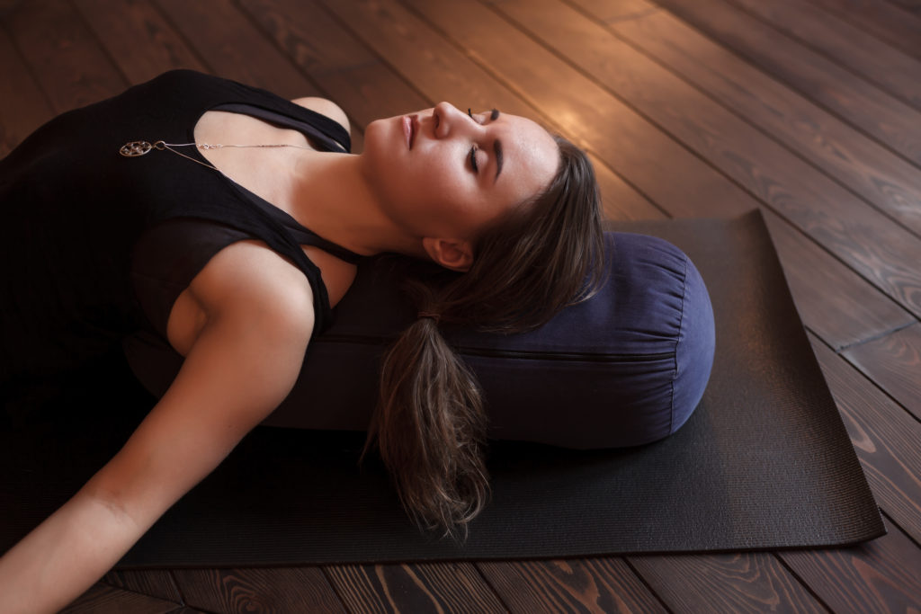 Woman resting after a yoga class in shavasana. Under back her bolster for spine therapy