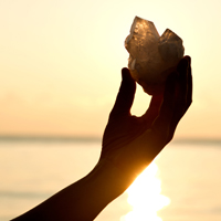 Woman's hands holding clear quartz point in front of the lake sunrise